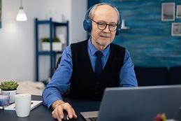 senior-businessman-listening-music-wearing-headphones.jpg