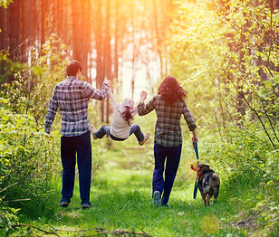 Happy family walking with dog in the for
