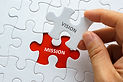 Hand holding piece of jigsaw puzzle with