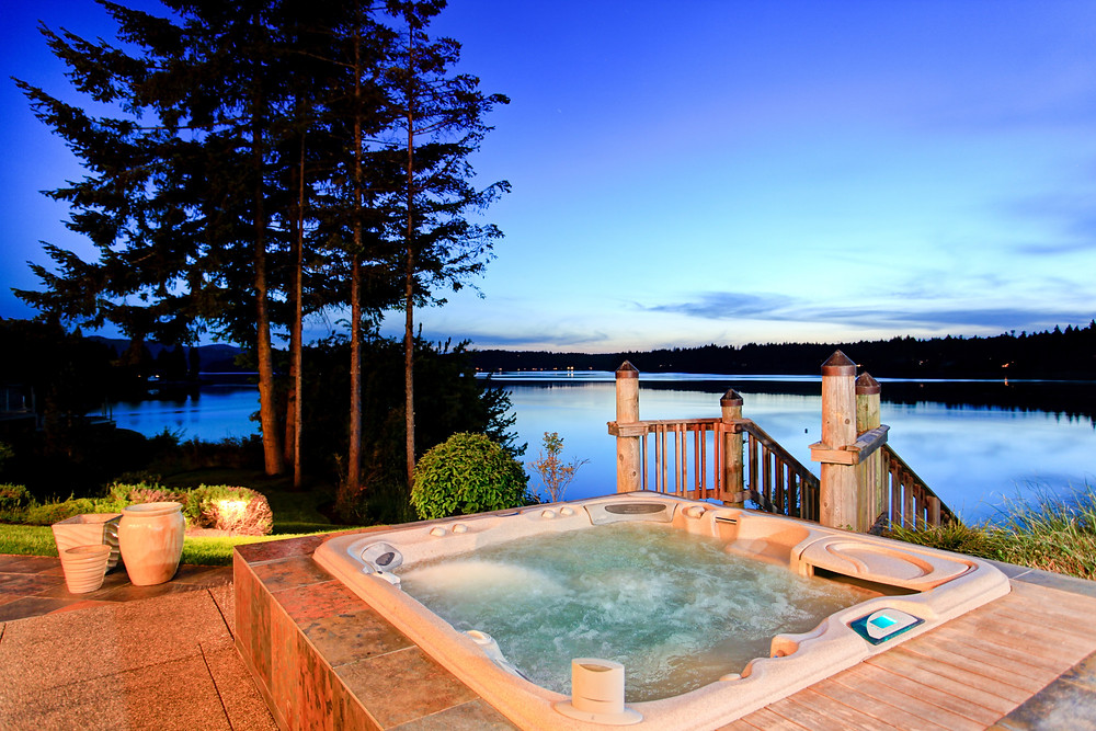 Hot tub on deck that is over looking a lake at dusk.