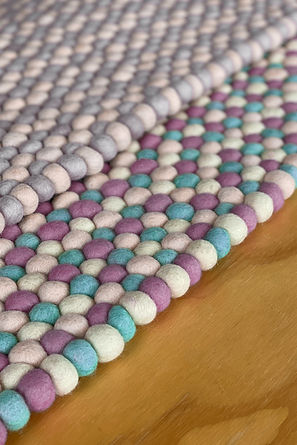 Multicoloured rugs wirth purple green ands grey textured balls.