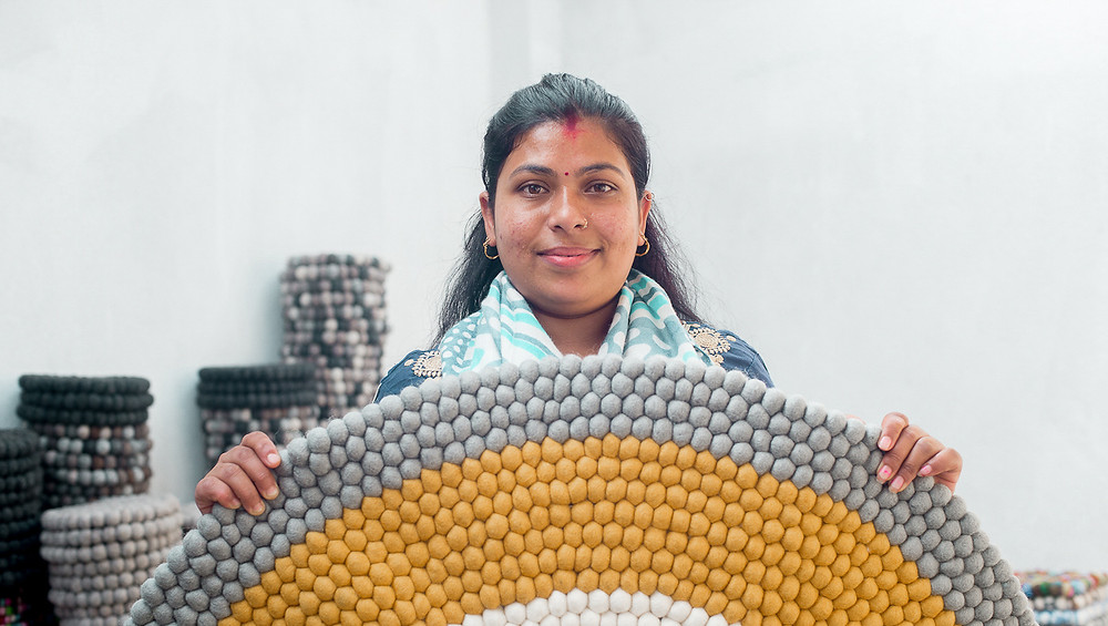 Woman holding up a grey and yellow rug.