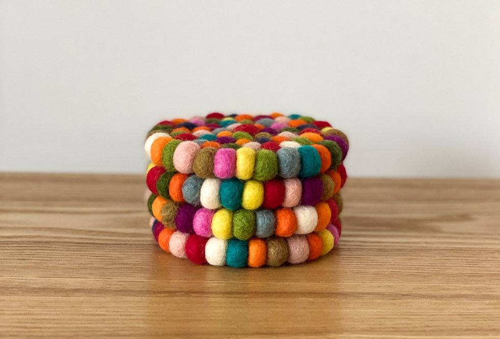 Multi coloured coasters made from felt balls.
