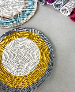 Yellow, grey, blue and white textured round rugs.
