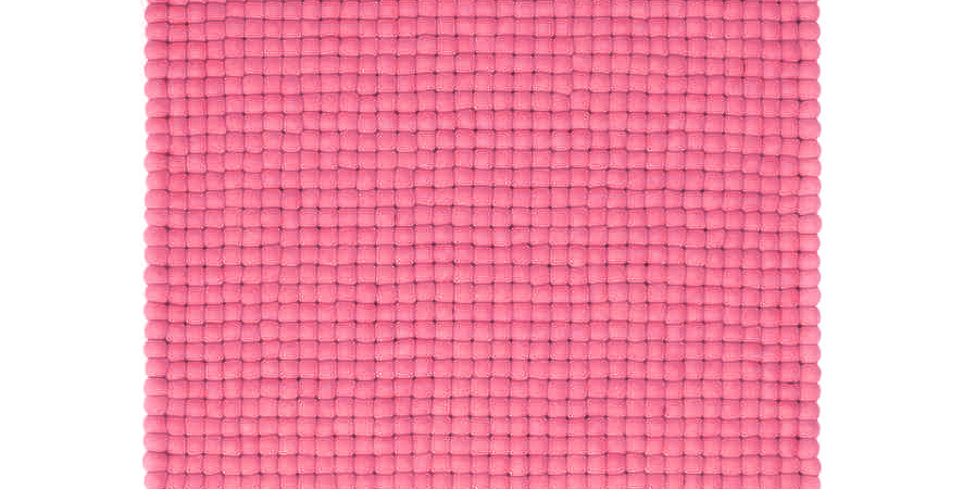 Bright pink felt ball rug full view.