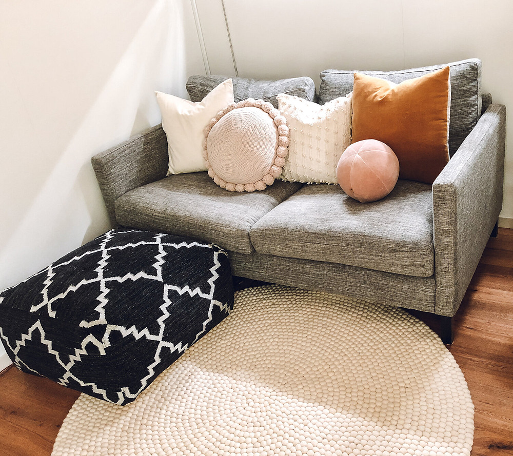 White rug with grey couch.