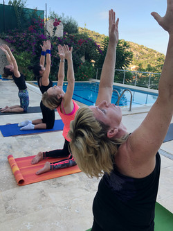 Students at Kalkan Yoga Retreat in morning class practice by pool, kneeling stretching arms over hea