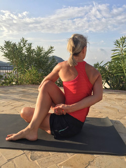 Yoga Teacher, Yogawithvickib, in Half Spinal Twist pose with hands clasped
