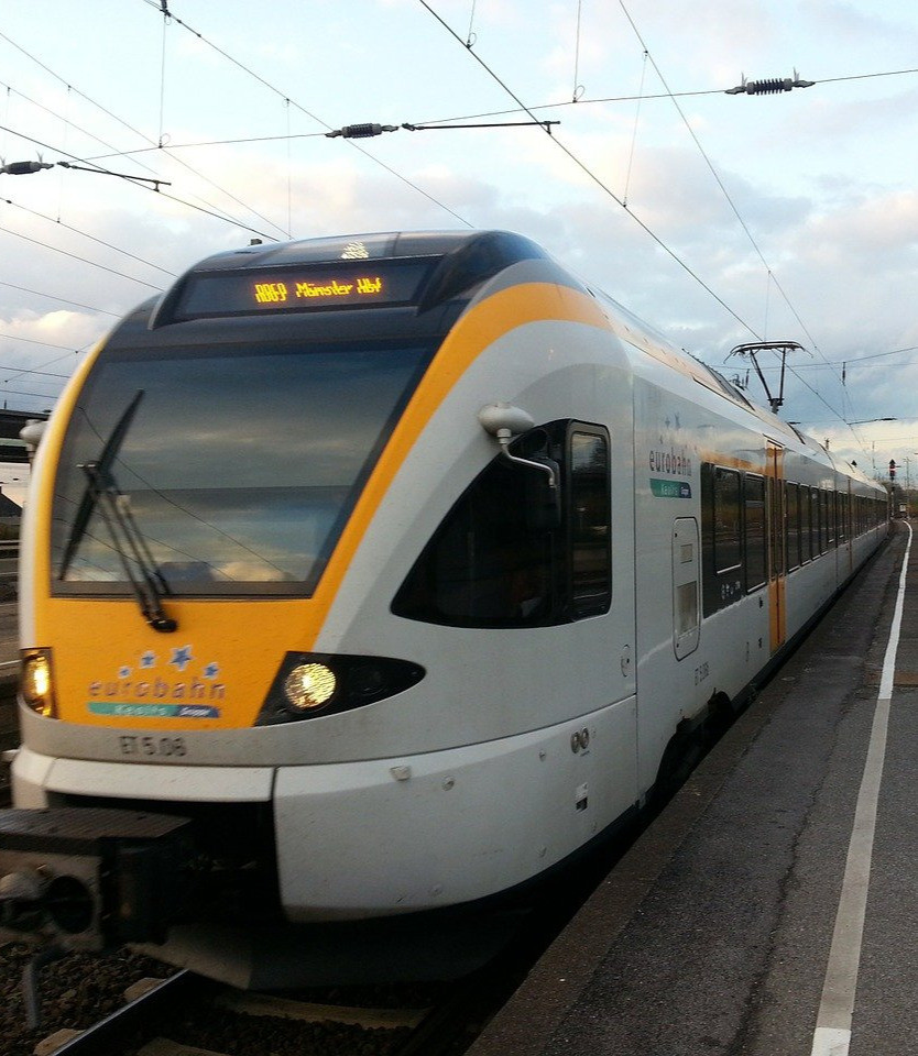 Yellow and white Euro Train on train tracks at a train stop in Europe