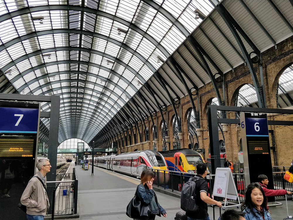 Train Station at Kings Cross, London. Trains waiting on platform. Platform numbers. People moving through station with luggage.