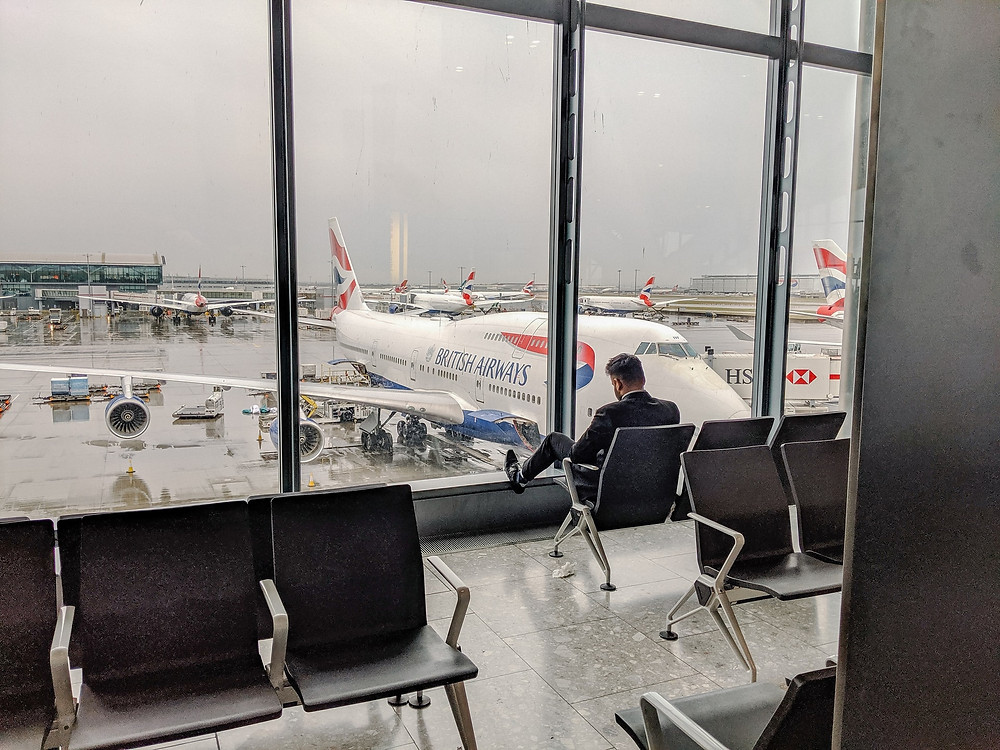 White, blue and red British Airways plane waiting to load plane man sitting reading and waiting in waiting area