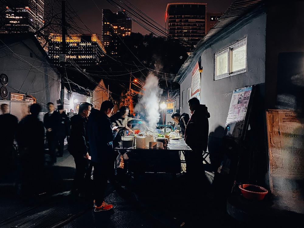 Comida sendo preparada em uma rua escura com pessoas observando.