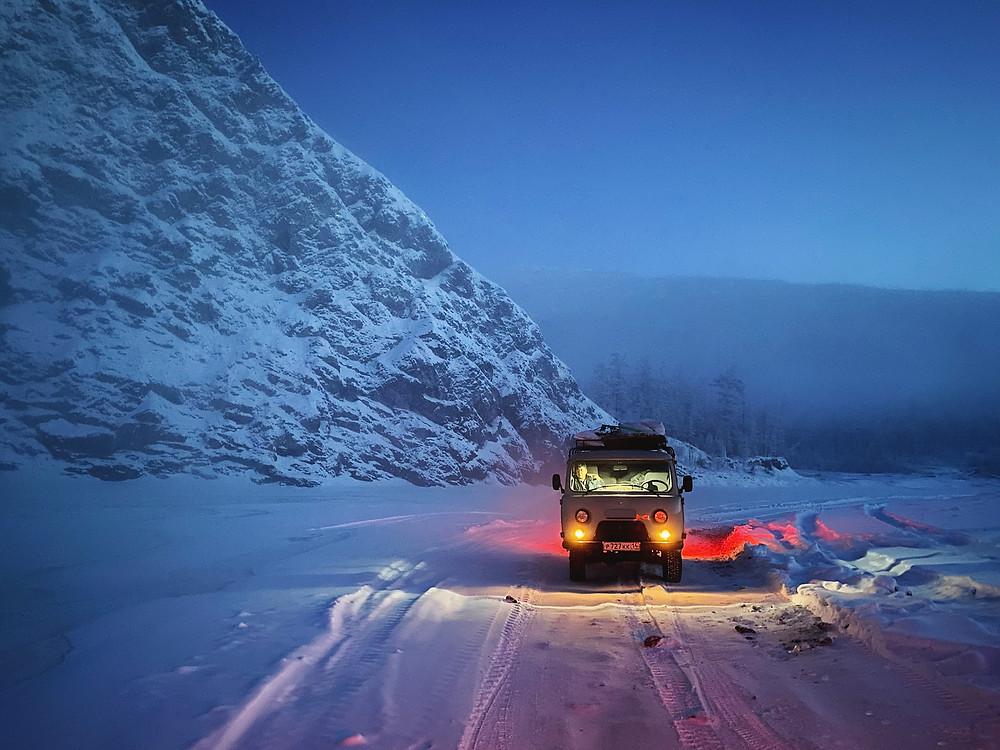 Carro em estrada ao lado de montanha com neve