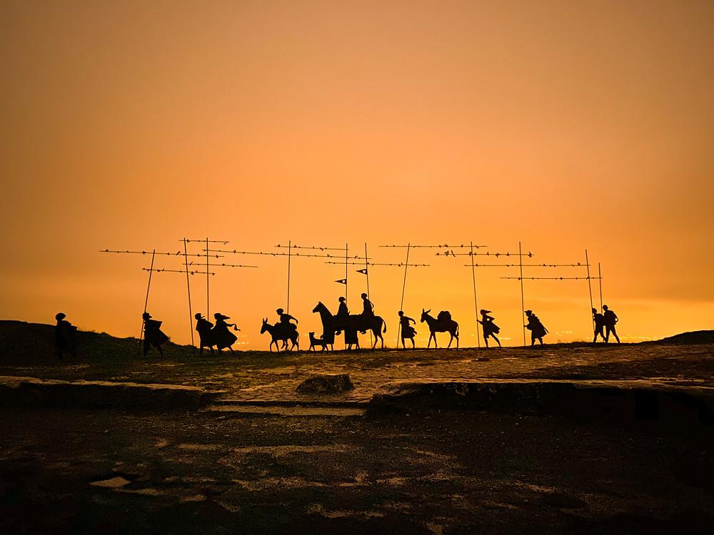 Peregrinos atravessando uma paisagem rochosa, recortada por um brilho laranja.