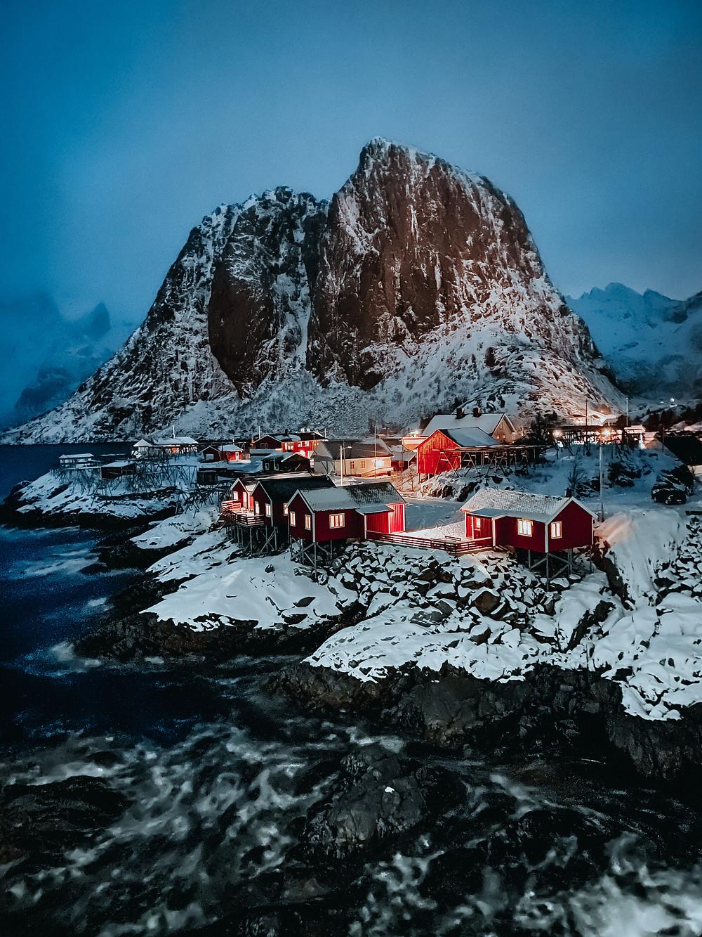 Pequena aldeia de cabanas vermelhas junto ao mar, com uma montanha de neve atrás delas.