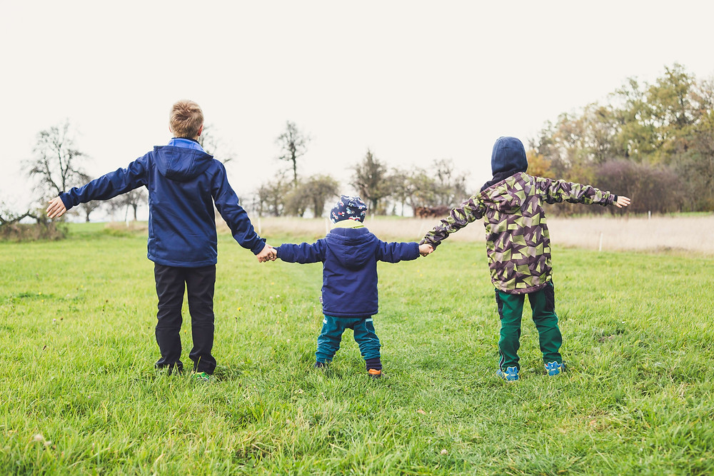 Three children outdoors in a grassy field holding hands. Photo by Markus Spiske on Unsplash
