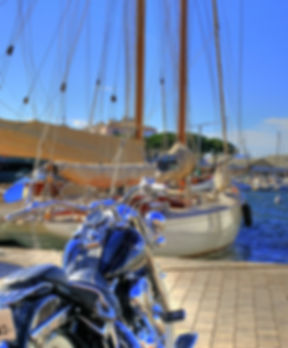 France Moto Road Trip - Moto dans un port devant un bateau accosté sur la Mediteranne - Circuit French Riviera et Saint Tropez à moto - francemotoroadtrip.com