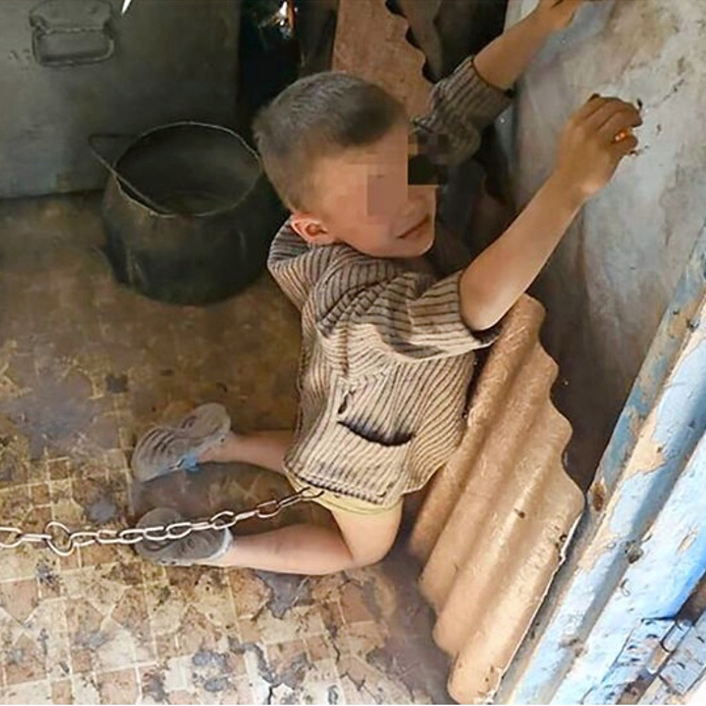 The child was found on his knees tethered to a door by shocked police in Ukraine.