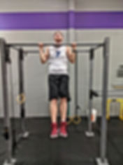 Personal training client doing pull ups during a workout