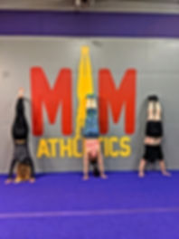 Students practing inversions during handstand class in Syracuse