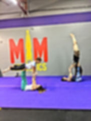 A community of studnts practicing acro yoga in syracuse
