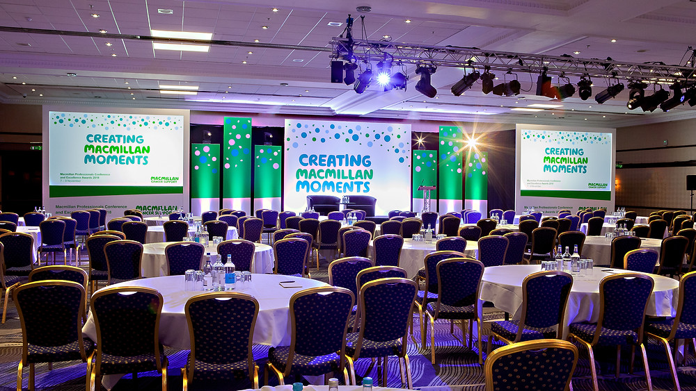 Front on shot of Macmillan event showcasing stage design, lighting, rigging, screens & truss.