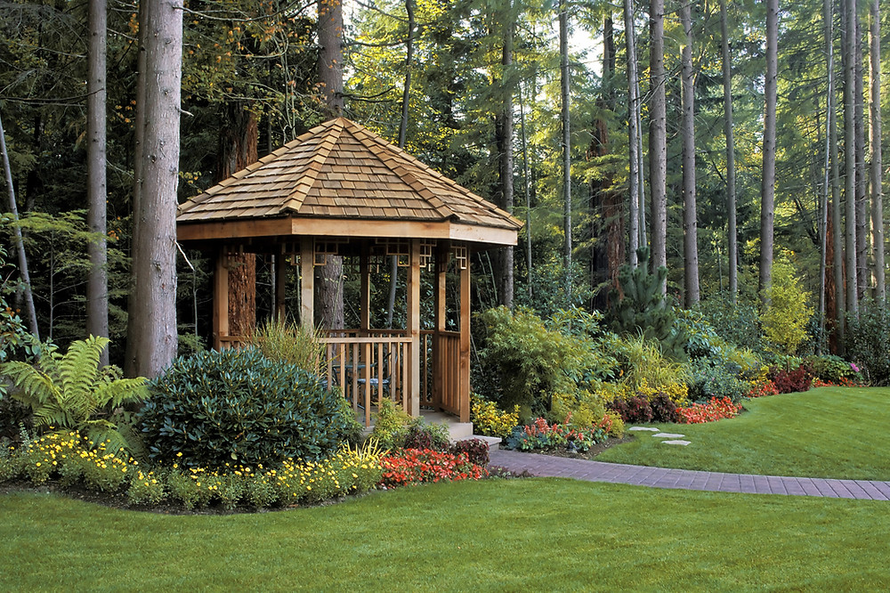 beautiful lawn and garden with spring flowers, a wooden gazebo, and freshly cut grass