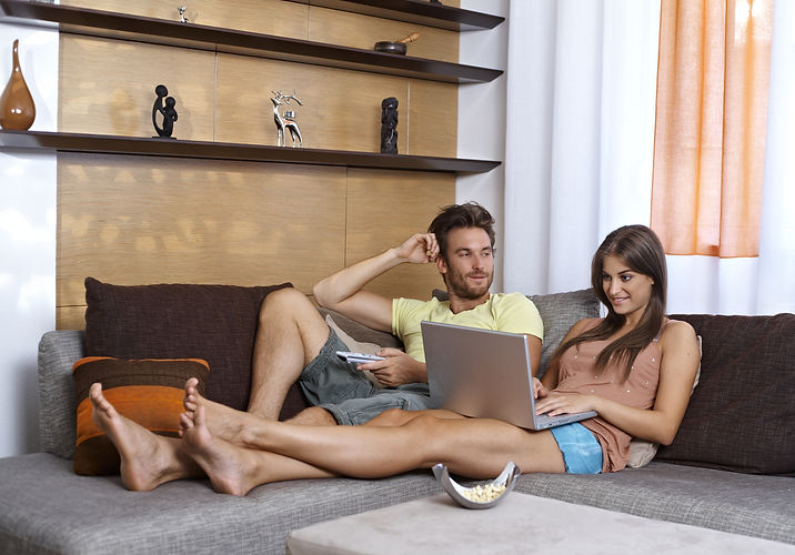 Young couple lying on couch, having rest