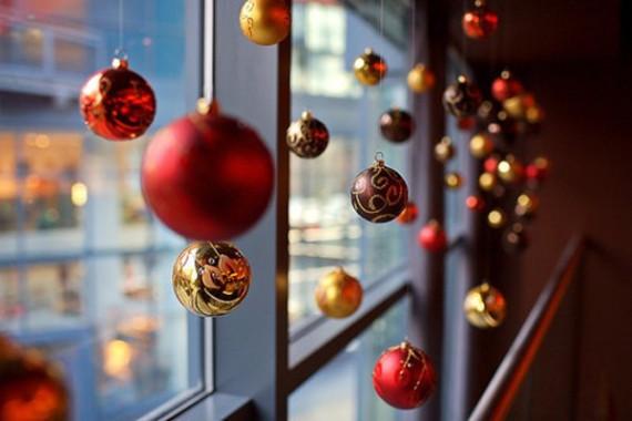 Ventana decorada con bolas navideñas en color rojo.