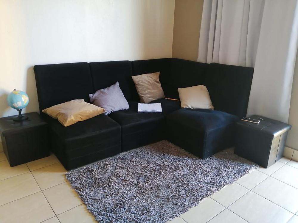 Sillón esquinero en color negro con alfombra gris y