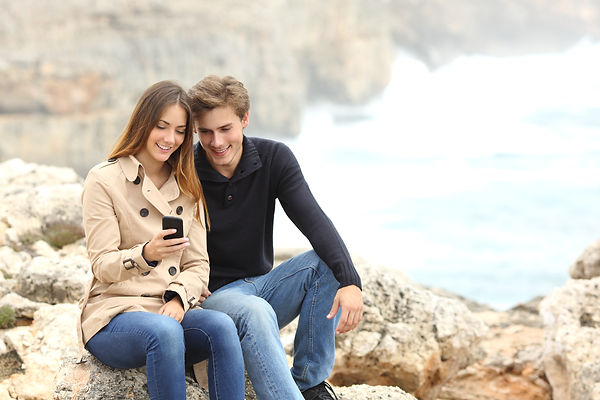 Couple sharing a smart phone on the beac