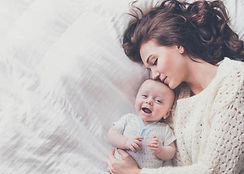 Mother Resting Next to Smiling Baby