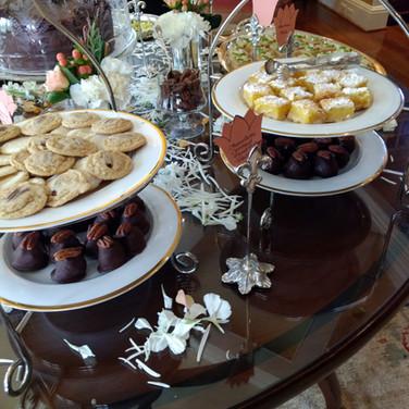 Top left tier - pecan dandies Bottom left tier -homemade Bourbon Balls Top right tier - homemade lemon bars Bottom right tier - Mint Julep Bourbon Balls
