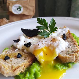 Uovo in camicia su crostino di pane all'aglio nero e crema di piselli