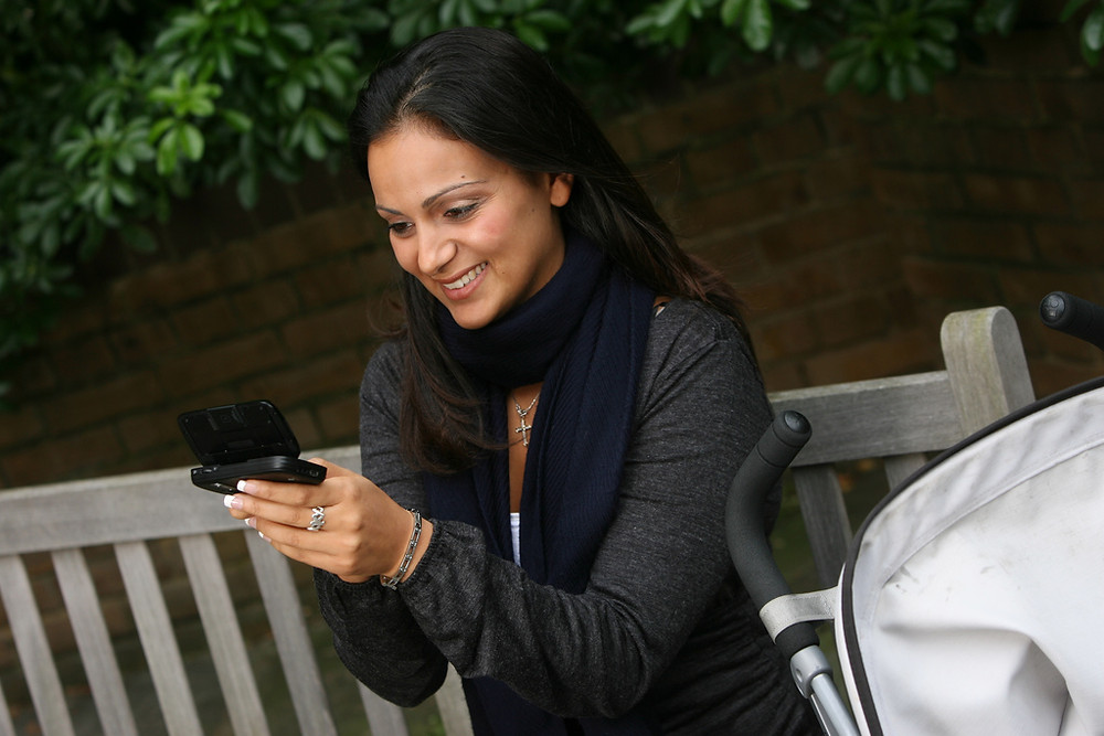 woman smiling at phone, texting, tweeting, Twitter