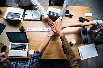 Company employees putting their hands together to show the power of teamwork
