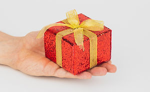 Close up of a person's hand holding a wrapped gift to give away