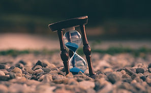 An hourglass sitting on rocky ground showing the passage of time