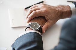 High level executive checking the time on his wrist watch while waiting for his coworkers who are late for the meeting