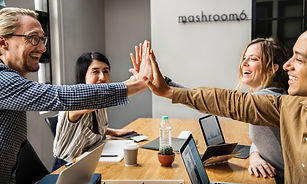 Company leadership team high fiving each other