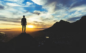 Person standing at the top of a mountain looking out at city below