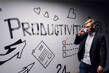 Company executive talking on the phone while walking past a wall that says Productivity