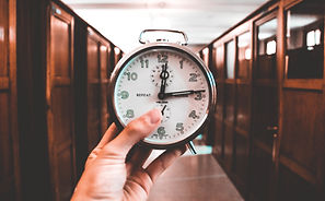 Close up of a person's hand holding up a big alarm clock that shows the time