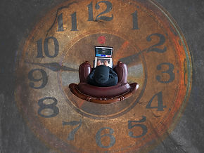 Entrepreneur working on his laptop while sitting in a chair in the middle of a big painting of a clock on the floor