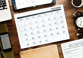 Busy business desk with calendar, clock, computer, phone, notes, and business newspaper