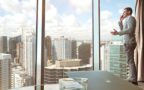 high-level organizational leader talking on the phone in modern corporate office looking out of window at tall city skyscrapers