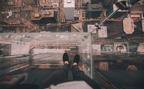 close up of person's feet standing at the top of a tall building looking down at the other tops of buildings