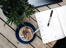 Daily meeting agenda of organizational leader on a desk with a cup of coffee