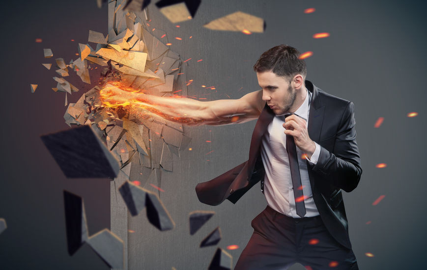 Businessman punching through a wall