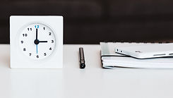 Clock on a table with time tracking agenda, pen, and phone